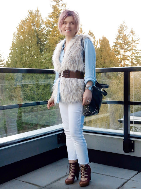 styling a chambray shirt and white jeans with lace-up shoes and a belted faux-fur vest
