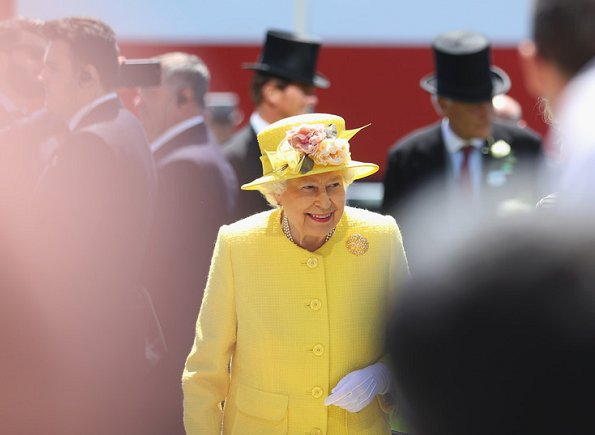 Queen Elizabeth arrived at the Epsom Derby in Surrey wearing a yellow coat, matching hat and flowery dress, holding a black bag