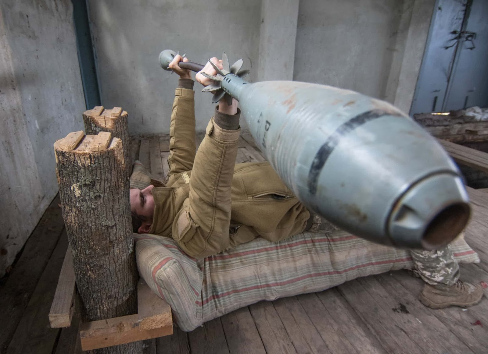25 Of The Most Intriguing Pictures Of 2017 - A Ukrainian serviceman exercises with weights made from mortars