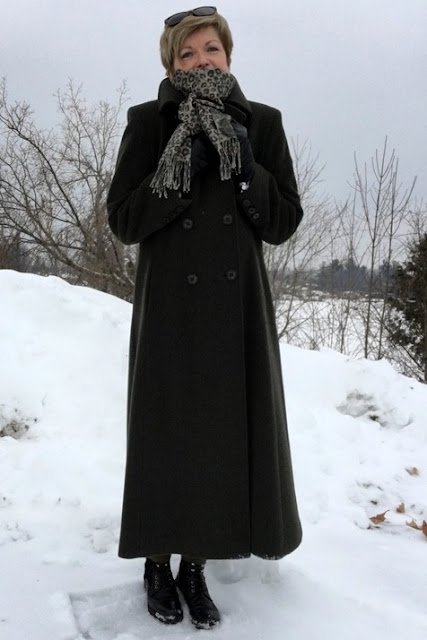 woman in front of snowbank in a long coat and scarf