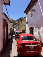 2 cars approach one-another from opposite directions on a narrow street