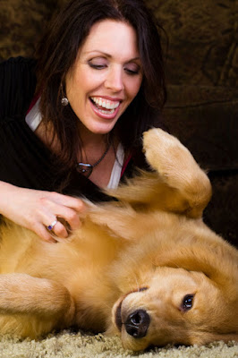 A woman gives tummy rubs to a relaxed Golden Retriever