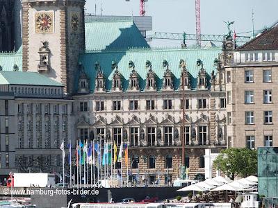 Frontansicht vom Hamburger Rathaus mit Fahnen davor.