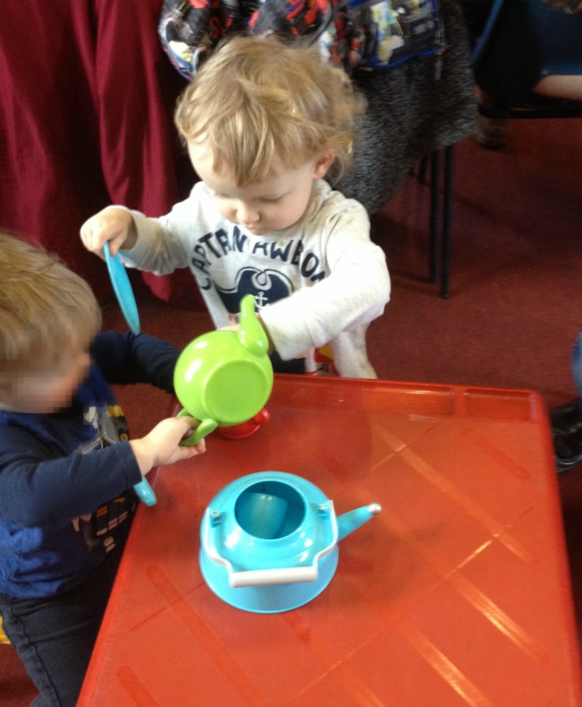 Two toddlers both wanting the teapot