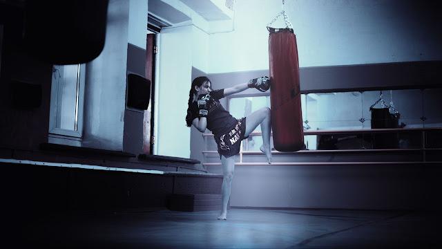 Woman practicing martial arts, heavy bag, punching bag, muay thai