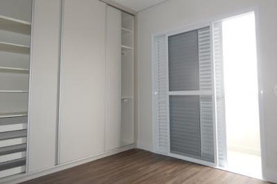 Armário embutido e ampla porta de correr na suíte com assoalho de madeira: iluminação natural e ventilação cruzada favorecida.