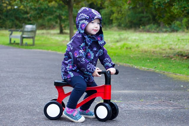 A toddler in a coat with hood up on a red plastic bike