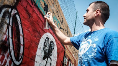 Picture of Ibo Omari transforming a swastika in Berlin, using spray paint. Photo by Deutsche Presse Agentur.