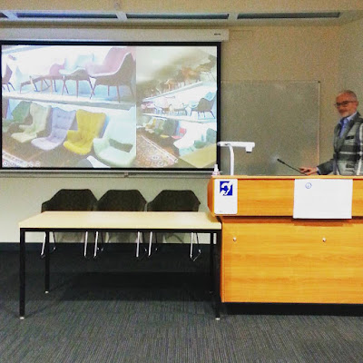 Geoff Isaac giving a talk in front of a slide showing how he stores his Featherston chair collection.