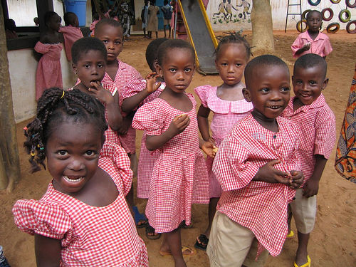 Elementary school children in Togo Africa playing games and eating snacks.