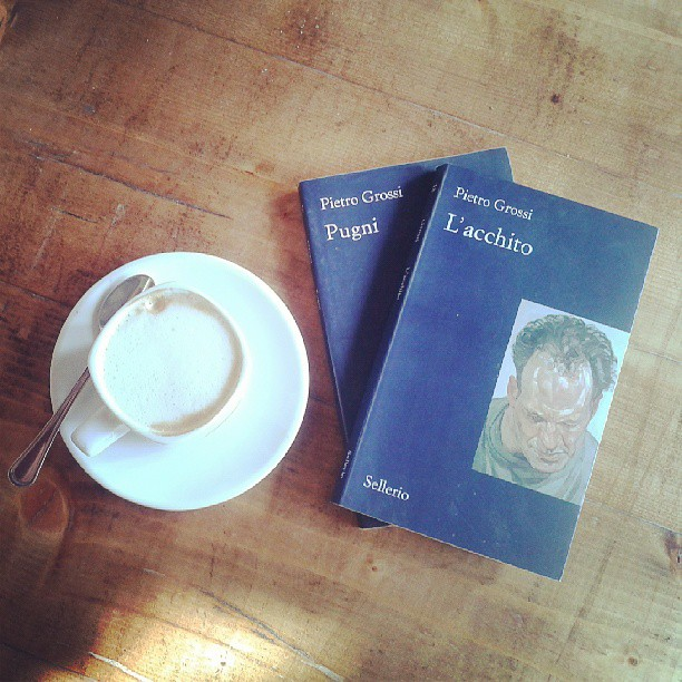 two Italian books and a cappuccino on a wooden table