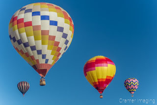 Cramer Imaging's fine art photograph of four colorful hot air balloons taking flight in Panguitch Utah with a blue morning sky