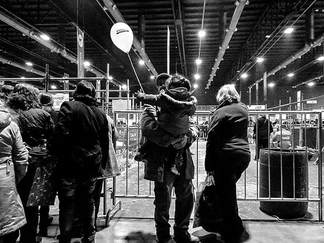 BYN.Interior exposición rural.Hombre sosteniendo a una nena con un globo en la mano