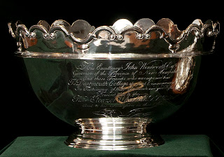 A silver bowl with scalloped edges and extensive text engraved on its side.