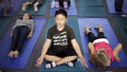 Niños practicando yoga en escuela