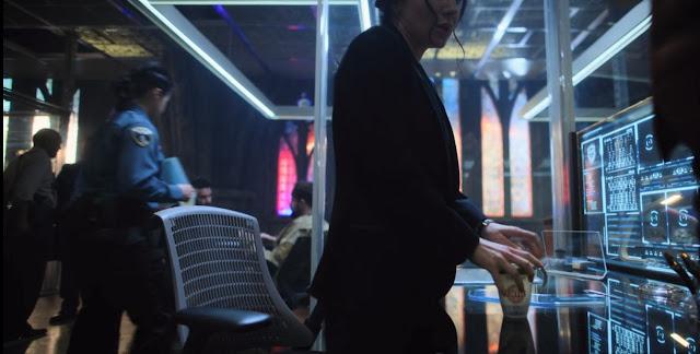 Ortega de pie, con la taza en la mano, ventanas tipo vidriera la fondo, pantalals luminosas con expedientes se reflejan en la mesa, gente de uniforme o sin el al fondo.