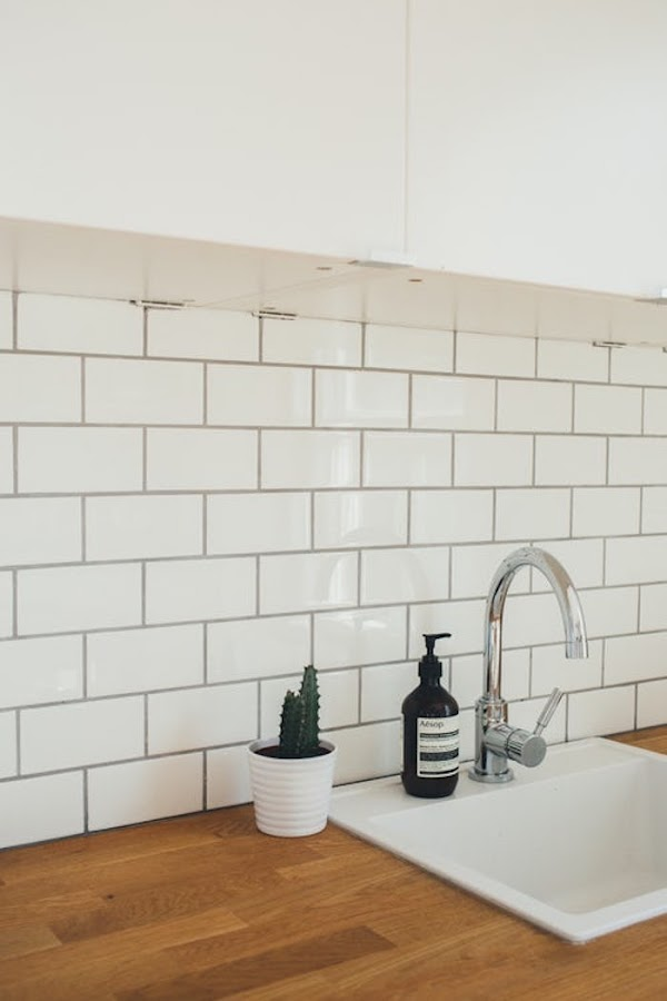Frente de cocina con azulejos tipo metro blancos y junta en gris. Encimera de madera y fregadero encastrado.