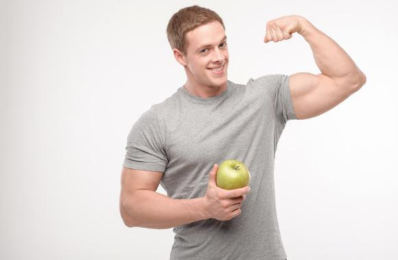 very athletic man flexing holding apple