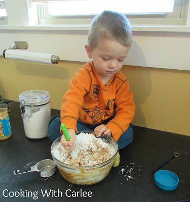 Little dude stirring a bowl of peanut butter center mixture