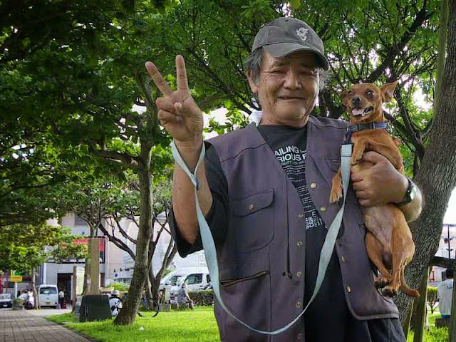 Homeless looking man holding a dog, smiling and giving the Peace Sign