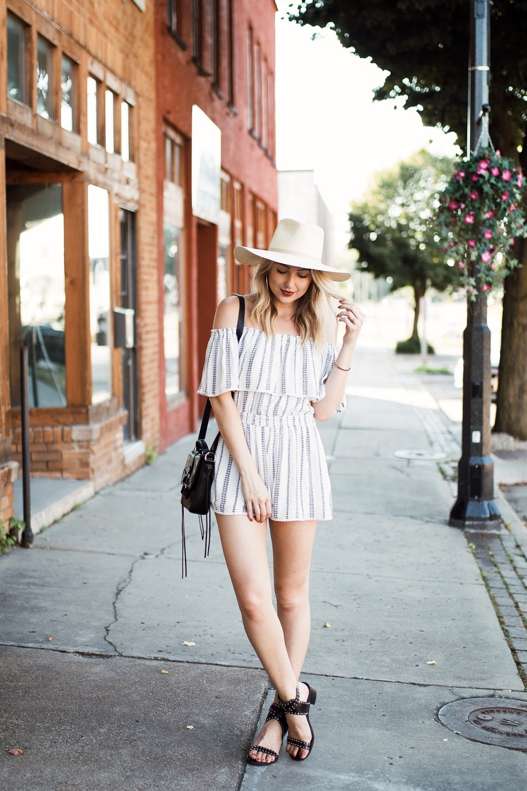 off-shoulder romper with a straw hat