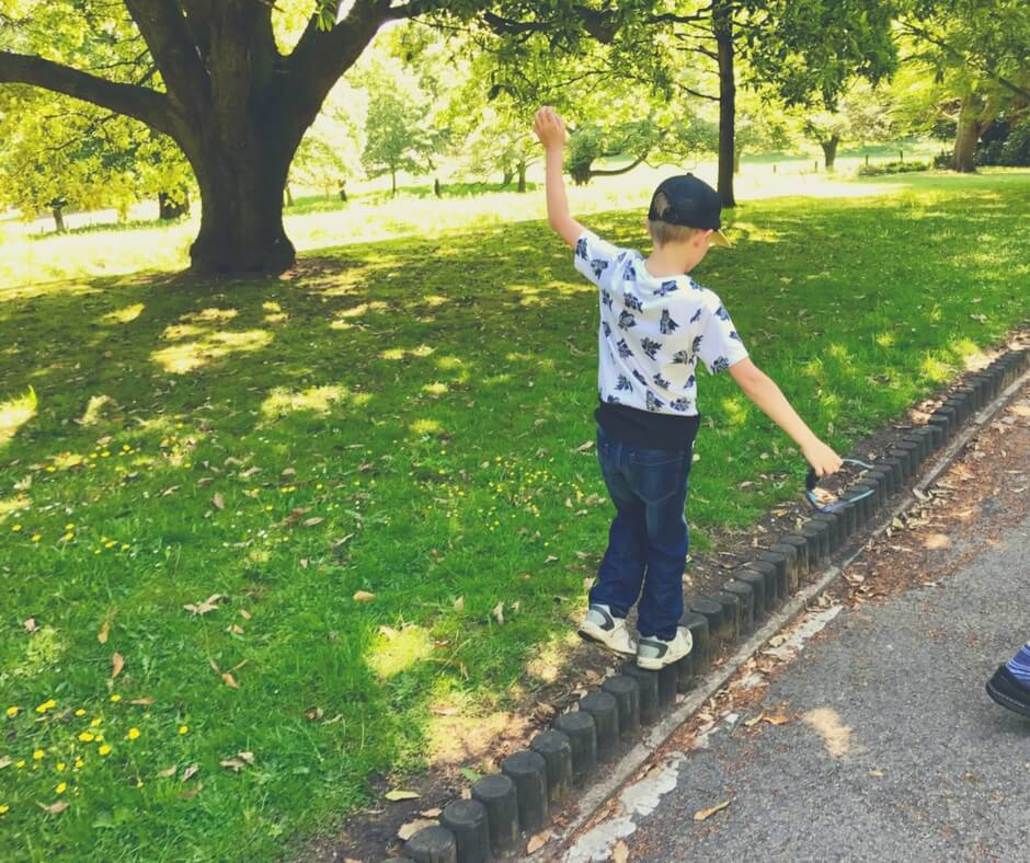 "A boy of 8, wearing a white Batman t-shirt and blue jeans with white trainers and a baseball cap on his head, is pretending to do tightrope walking along a wooden barrier than lines a pathway. The boy is holding his arms out to his sides to balance himself. The sun is shining down through the shades of overhead trees. There's the trunk of a large tree in the background. Image for ""How well do you know your children?"""