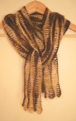 Woodlands scarf: wavy-stripes in browns and greens hanging on a coathanger as if it were around the neck.