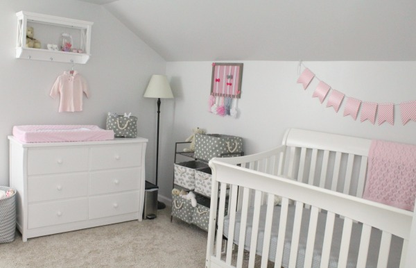Gray white and light pink nursery for a baby girl in a small corner of a converted attic