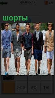 По улице идут несколько молодых людей в модных шортах, демонстрируя одежду