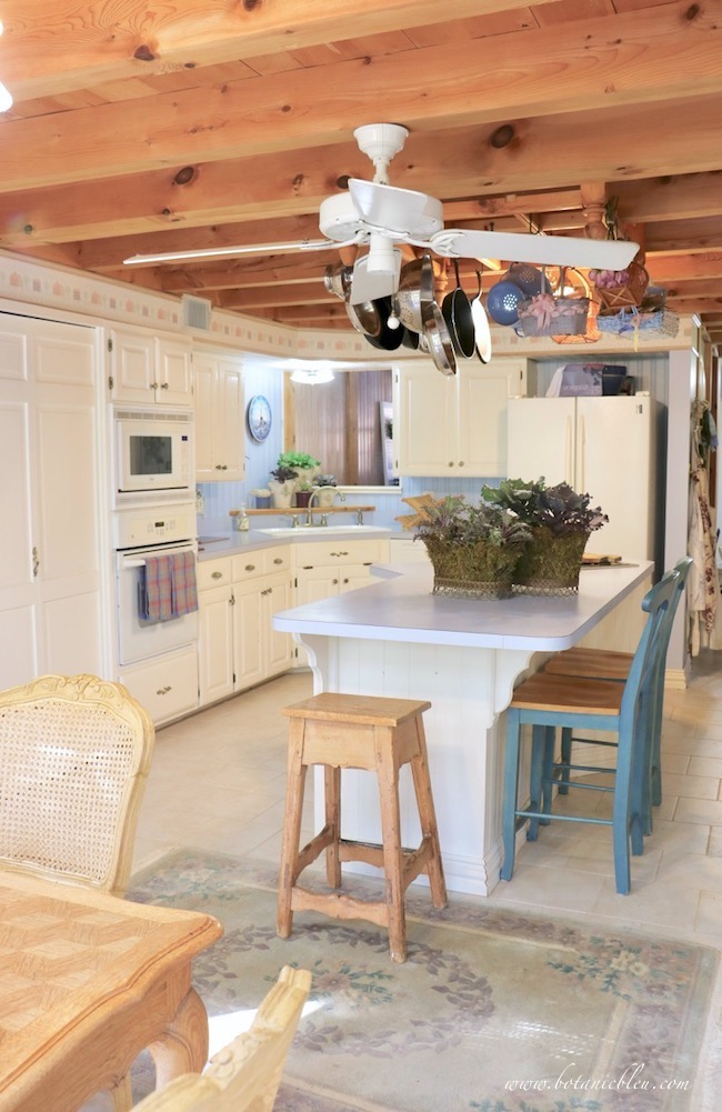 french country kitchen with natural colored pine ceiling and pot rack decorated with ornamental kale for fall