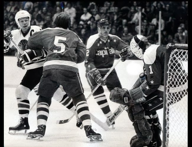 Vs. Chicago: Willy Brossart (5), Jack Lynch (2) defend, as Ron Low makes the save; Caps won 7-5, the first W of their 2nd season (10/26/75)