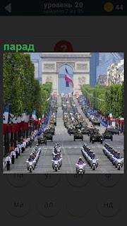 По главной улице города идет парад, впереди мотоциклы, далее техника