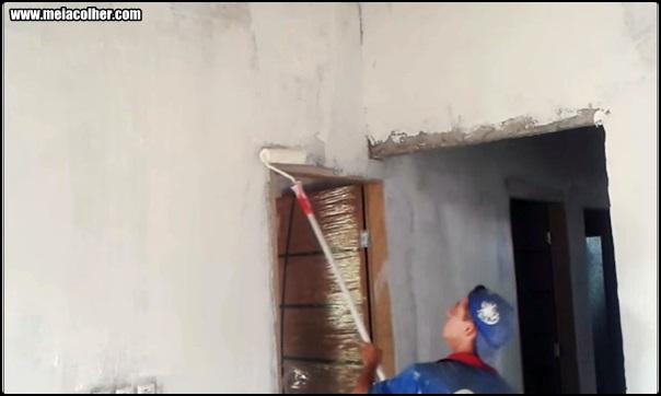 aplicando massa corrida na parede com rolo