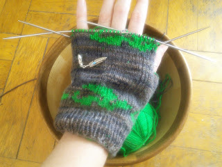 Someone wearing a partly-finished fingerless glove.  The glove is brown with a green motif around the wrist.  Underneath their hand is a wooden yarn bowl with the balls of yarn inside.