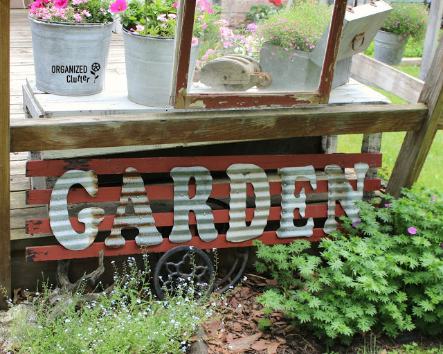 Cool I added some galvanized letters to one of the shutters and placed it in my junk garden