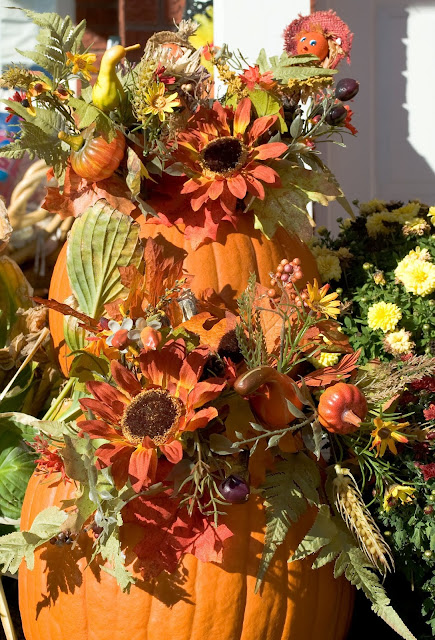 A display of pumpkins surrounded by fall florals deck the front steps in autumn and fall.
