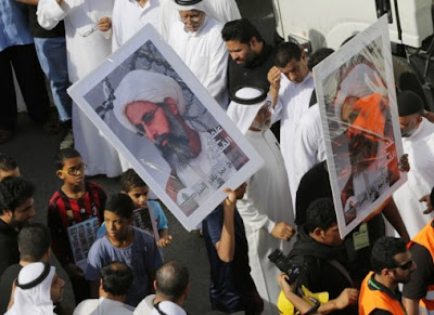 Saudis carry a poster demanding freedom for jailed Shiite cleric Sheikh Nimr al-Nimr