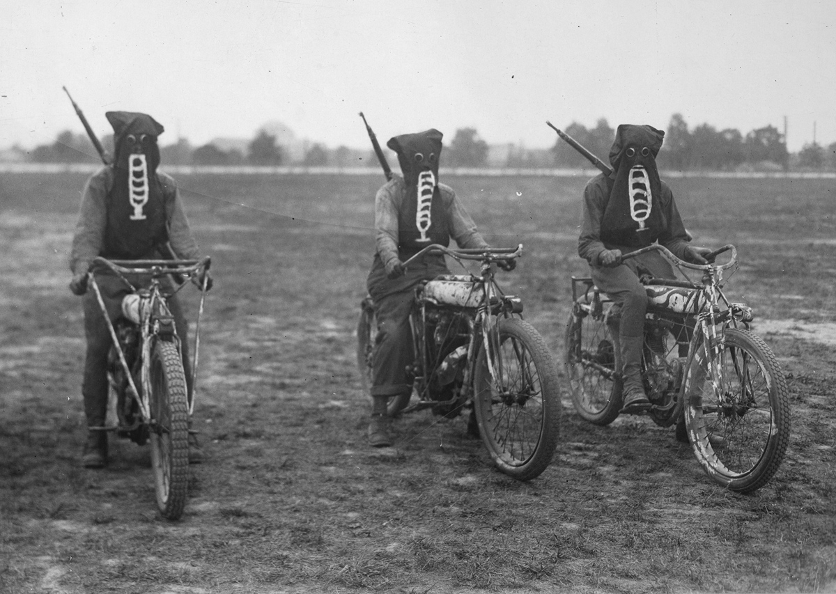 Original caption: Three motorcycle dispatch bearers in training at the U.S. Training Detachment School in Richmond, Virginia, wearing their gas masks, ready to start on a dispatch carrying trip in an exhibition.