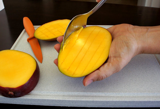 A hand holding a slice of mango using a spoon to scoop out the mango slices from the skin