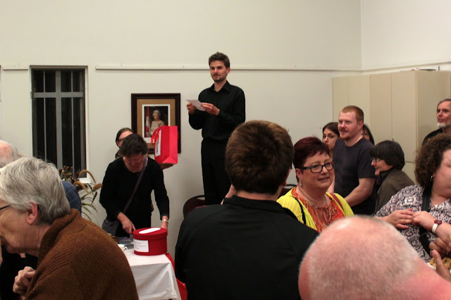 Alasdair stands on a chair to see over the crowd and announce the door prize winner