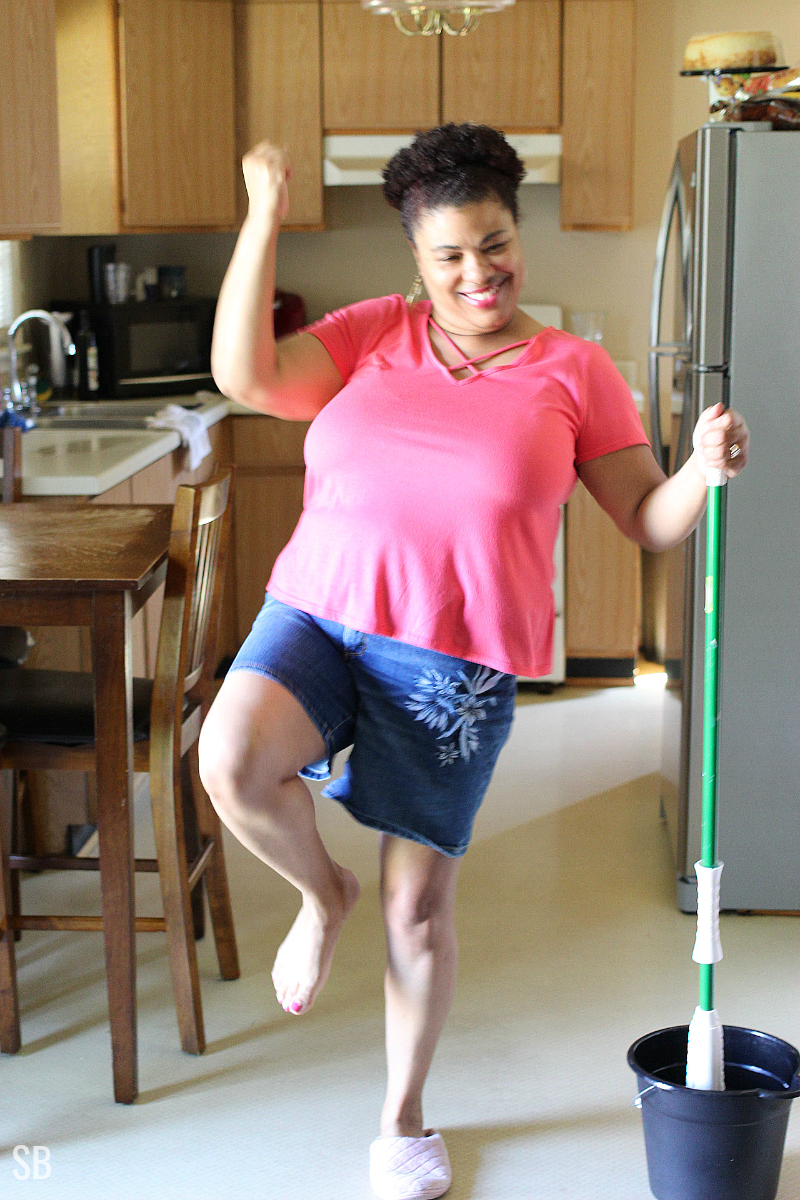 a woman dancing while mopping the floor