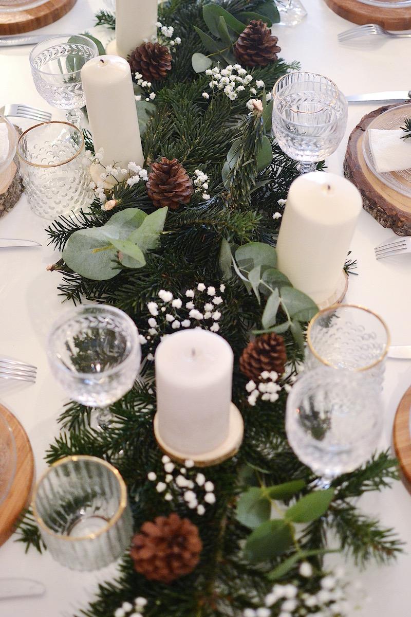 centre de table blougie blanche, feuille d'eucalyptus, pigne de pin et gypsophile, branche de sapin