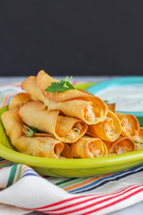 These delicious shrimp taquitos are baked, not fried, and full of incredible flavor. Served with a side of creamy salsa verde dipping sauce, this is the perfect appetizer to serve for the big game!