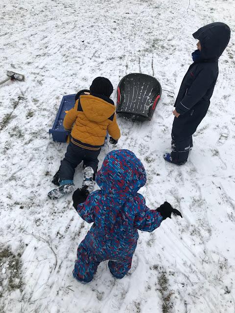 Schnee Schlittenfahren Winterkinder Winter Aktivitaeten vor der Haustuer