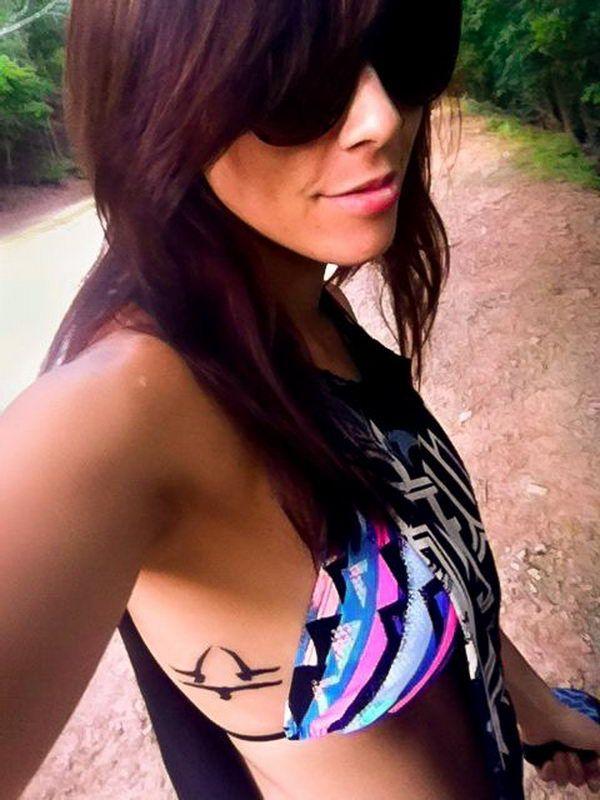 Mujer morena en el bosque, lleva gafas de sol y sonrie, tiene en sus costillas tatuaje con tres palomas formando signo de libra