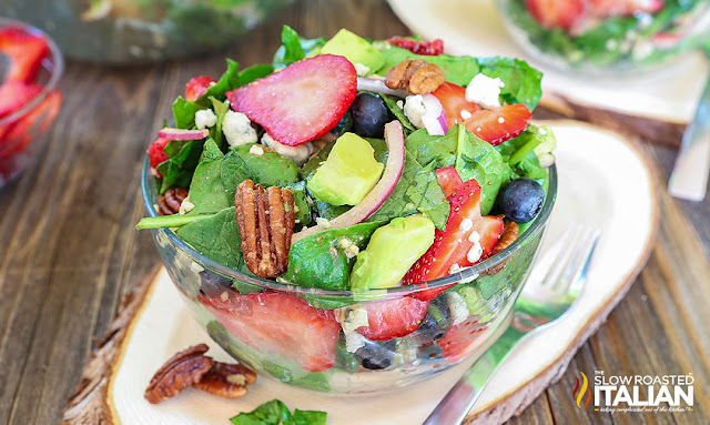 strawberry walnut salad in a bowl with blueberries and avocado