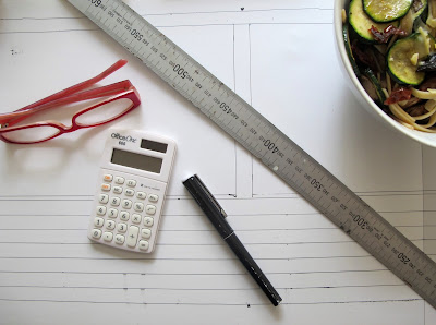 Reading glasses, metal ruler, calculator, pen and bowl of pasta on top of a piece of paper with a plan for a wall with windows.