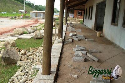 Execução dos pisos externos nos terraços com a soleira de pedra folheta e na parte interna o piso com pedra caco de São Tomé. Nas paredes a alvenaria de bloco já rebocado com reboque rústico com as janelas de madeira com os batentes de dormente de madeira.