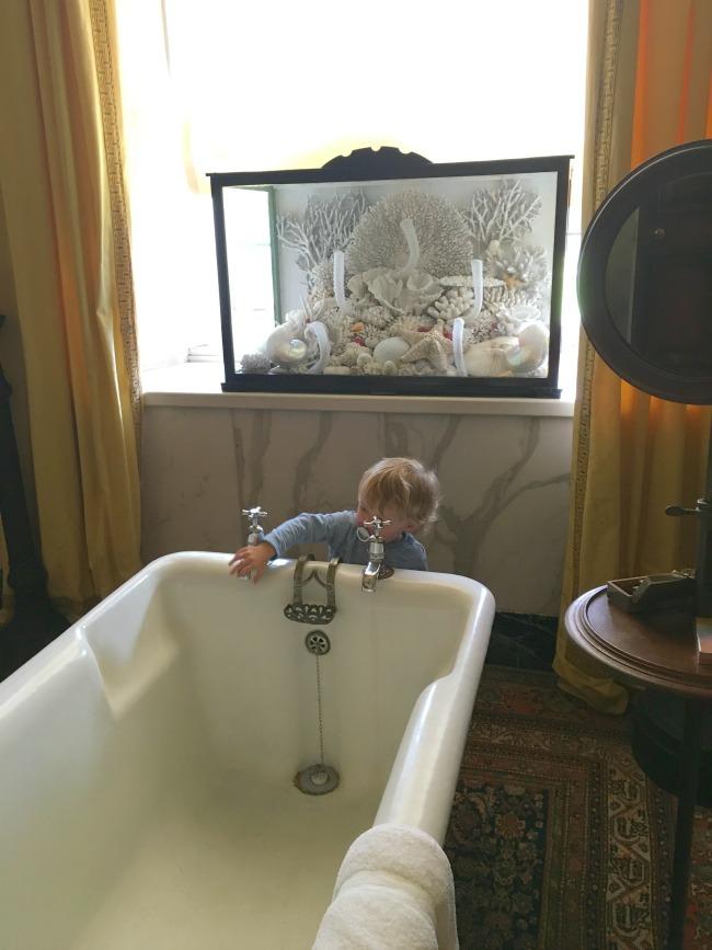 toddler-stood-by-huge-bathtub