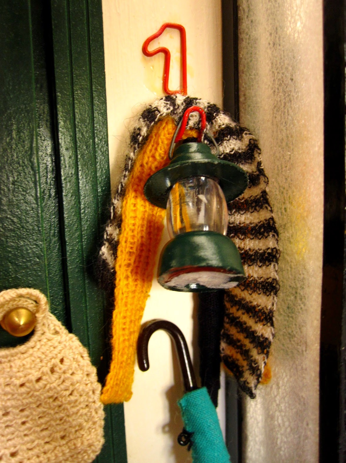 Modern dolls' house miniature wall hook holding two knitted scarves, a lantern and an umbrella.